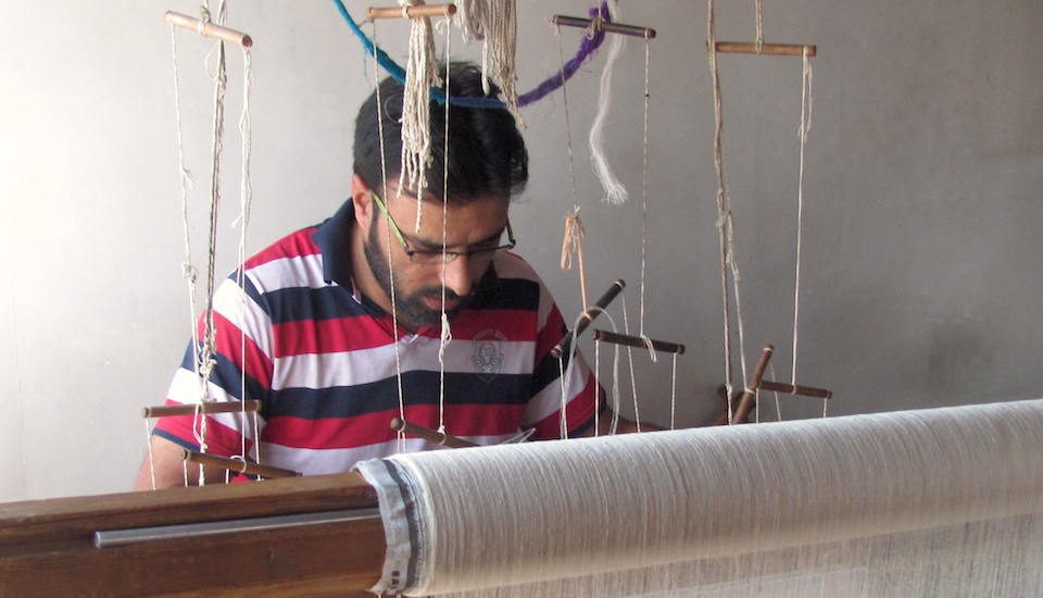 A Kashmiri artisan weaving a Pashmina shawl on his handloom. (Photo by Athar Parvaiz)