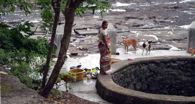 A village woman in Elephanta cleans household utensils at a well that barely contains any water. (Photo by Gajanan Khergamker)