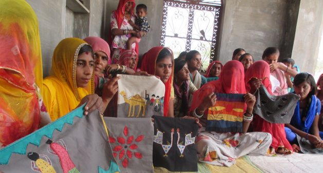 Women embroiders show their latest work after a training workshop. (Photo by Tarun Kanti Bose)