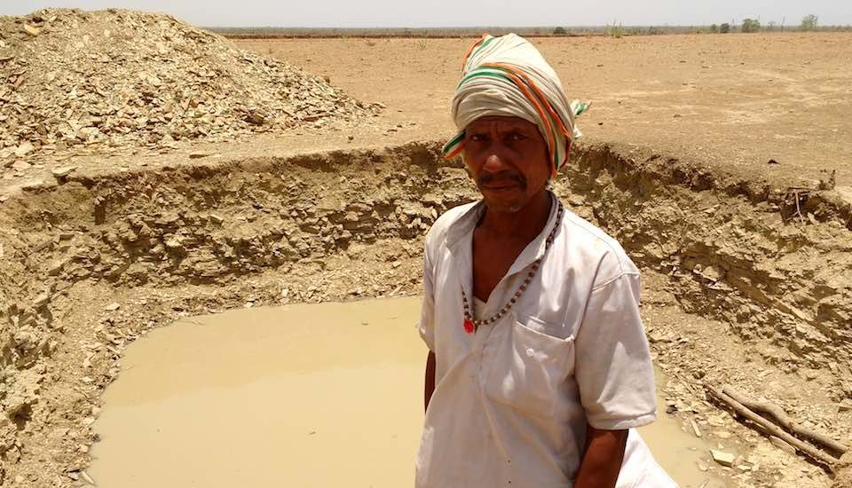 Pooran Adivasi near his farm pond with some water, even as the rest of the landscape wears a parched look. (Photo by Nachiket Sule)