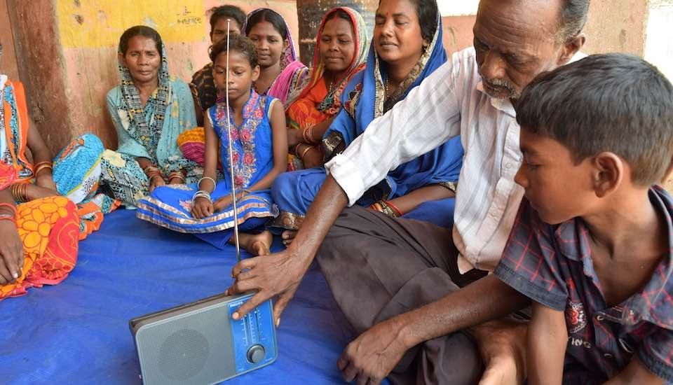 Residents of Adakata village listen to a program on community radio. (Photo by Basudev Mahapatra)