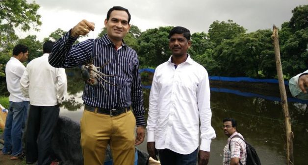 Vivek Vartak, inland fishing workshop coordinator, with a crab caught in farmer Khamkar's pond. Fish seeds and fingerlings being distributed to farmers. (Photo by Kharland Research Centre)