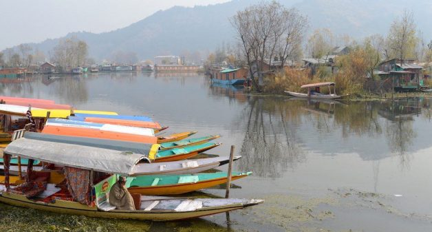 A boatman in Dal Lake warms himself with a fire pot under his pheran cloak. Credit: Athar Parvaiz