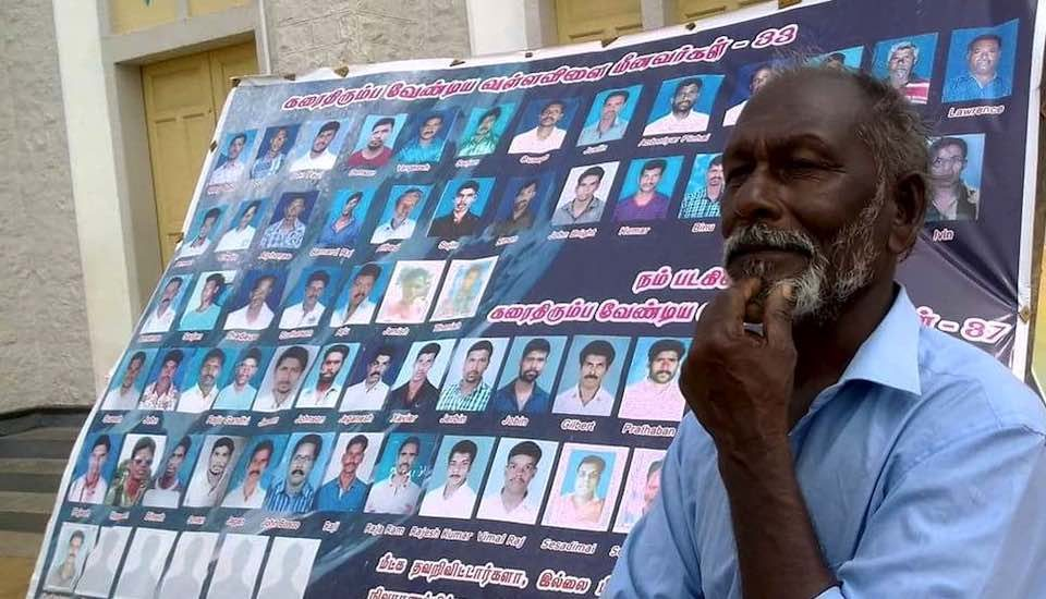 Fisherman Amaladasan stands beside a poster showing photos of 70 fishermen missing from Vallavilai village in Kanyakumari district since Cyclone Ockhi. (Photo by M M Paniyil)