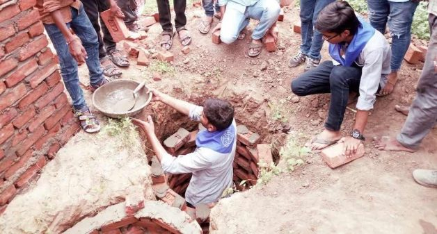 NSS volunteers are seen constructing a toilet pit. (Photo by Gajanan Khergamker)