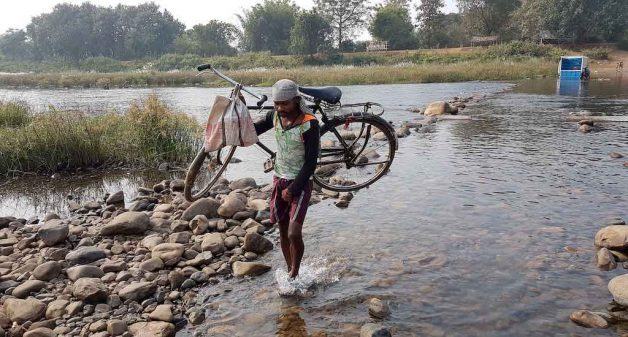 Villagers like Basant Mahakud of Hinjli routinely cross the river, often carrying their bicycles, to reach their work place and hospitals (Photo by Manish Kumar)