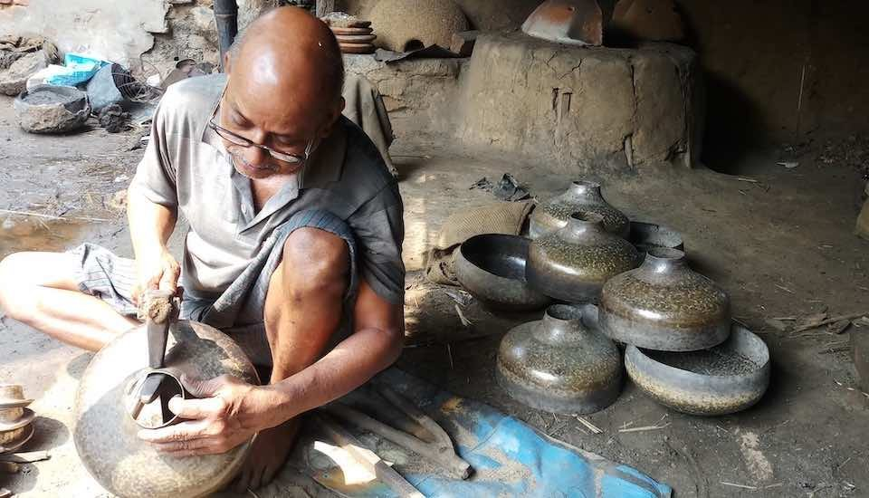 A brass smith beats into shape a traditional brass pot that is no longer in demand (Photo by Gurvinder Singh)