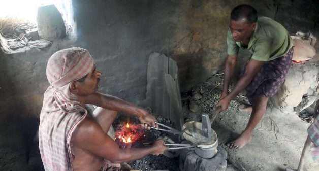 Brass smiths like Budhodeb Hazra spend hours at the furnace to make traditional brass pots (Photo by Gurvinder Singh)
