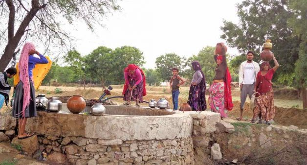 Women face risks by standing on the rim of wells, or on dilapidated low walls, while drawing water from wells (Photo courtesy AmritaServe)